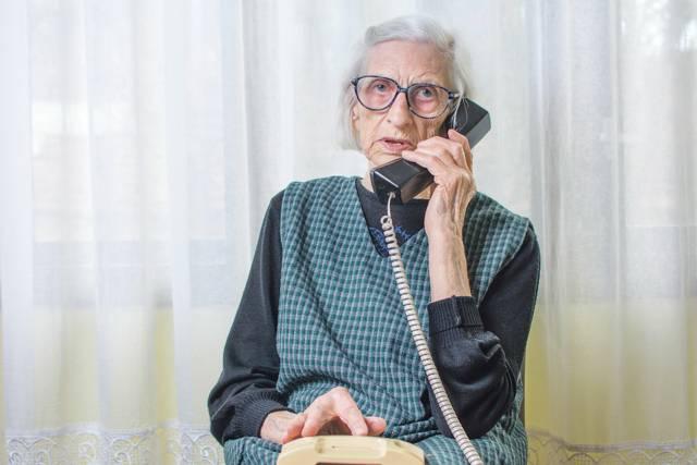 Eine ältere Dame mit einem Telefonhörer in der Hand